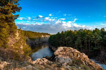 view from the cliff to the river flowing in the canyon. top view of the river and pine forest