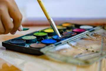 Watercolor palette  with brightly colored paints and brush used by child to paint at home. The concept of stay creative at homes during coronavirus or COVID-19 lockdown.