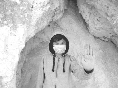 Boy in a medical mask on a background of chalk mountain. Coronavirus Infection Pandemic Protest (COVID-19). Black and white photo