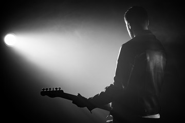 Rock guitarist man in leather jacket standing his back in smoky studio or stage masterfully playing electric guitar. View of unrecognizable musician in the spotlight.