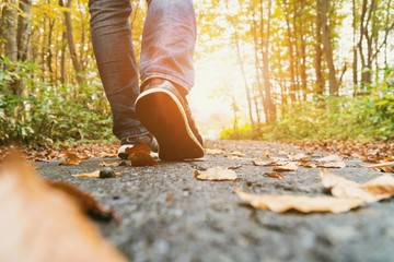 Low Section Of Man Walking On Road In Forest During Autumn