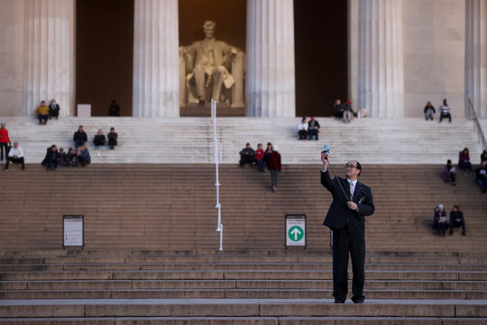 A man holding his Bible takes a selfie as he waits for Easter sunrise at the Lincoln Memorial during the coronavirus disease (COVID-19) outbreak in Washington