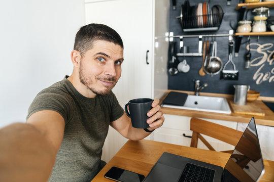 Handsome man taking selfie while working on laptop at home in modern loft kitchen. Remote work.
