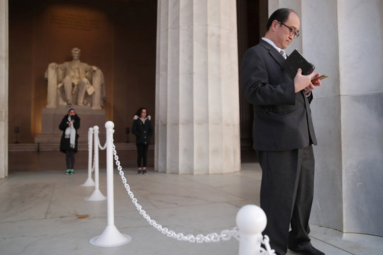 A man holding his Bible waits for Easter sunrise at the Lincoln Memorial during the coronavirus disease (COVID-19) outbreak in Washington