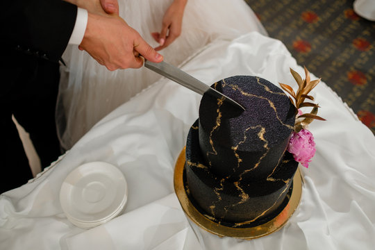 Bride and groom cut the wedding cake.