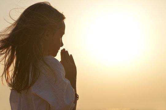 Portrait of little girl praying on light background