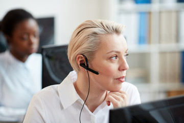 Close up portrait of blonde woman wearing headset and talking to customer while working in support service call center, copy space