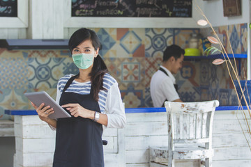 Portrait of waitress using digital tablet and wear face masks