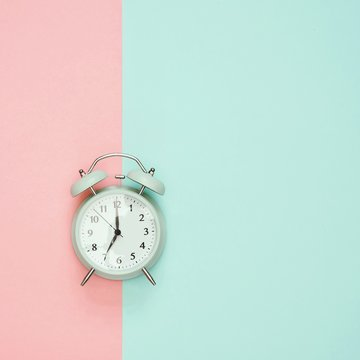 Directly Above Shot Of Alarm Clock Against Colored Background