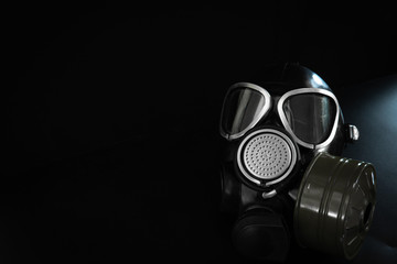 Military gas mask with a filter box on a black background. Personal respiratory protection from dust, toxic substances and viruses. Place for text.