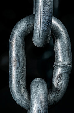 One chain link. Links of a metal chain close-up on a dark background.