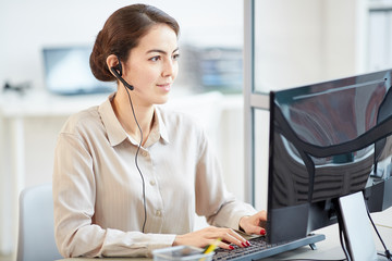 Portrait of elegant businesswoman wearing headset while using computer at desk in office, copy space
