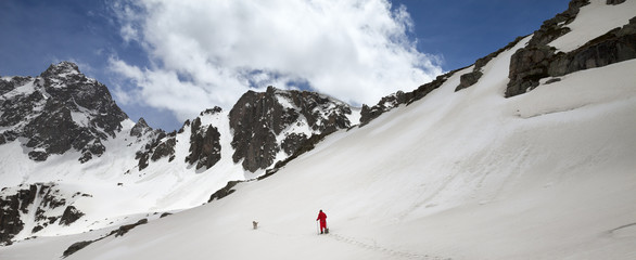 Fototapete - Hiker in snowshoes with dog in high snowy mountain
