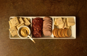 Horizontally Pictured Rectangular Serving Plate of Cheese, Crackers, Meats, and Mustard