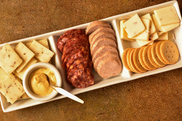 Rectangular Serving Plate of Cheese, Crackers, Meats, and Mustard, Pictured Diagonal