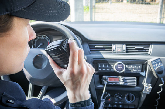 Microphone of a radio or walkie-talkie in the hand of a female police officer in her patrol police car.