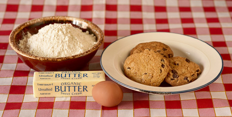 Chocolate Chip Cookies, Butter, an Egg, and Pastry Flour on a Checkered Table Cloth