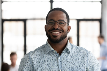Headshot portrait of smiling African American male employee in glasses look at camera posing at...