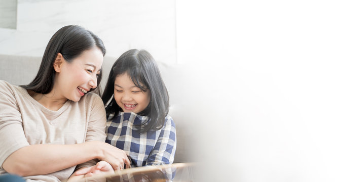 Mother and her daughter child girl playing her mom in sofa living room at home. Happy Asian family concept