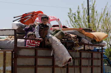 Displaced Syrian children ride on a back of a truck as they move back home, as some people are afraid of the coronavirus disease (COVID-19) outbreak in crowded camps, in Dayr Ballut