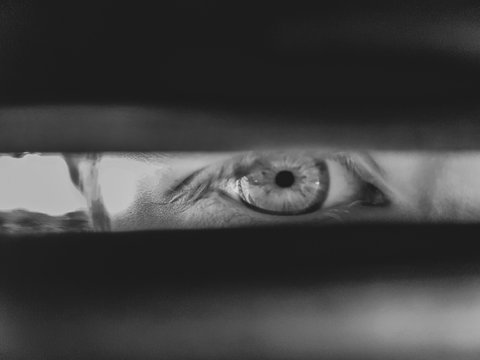 Close-up Portrait Of Mid Adult Man Looking Through Window Blinds