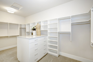 Huge walk-in closet with shelves, drawers and clothes rails. Luxury American modern home.