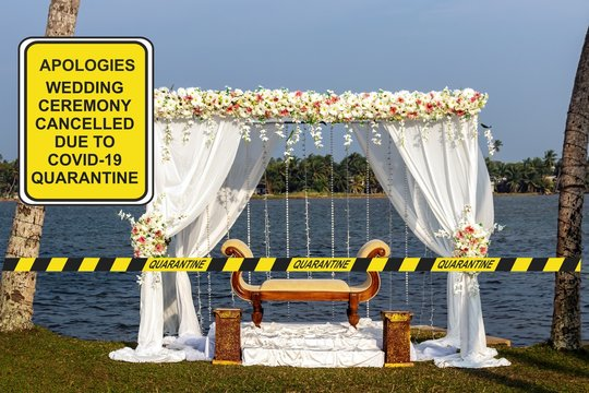 ''Apologies. Wedding ceremony cancelled due to COVID-19'' notice against a decorated weding tent with a stretched quarantine tape