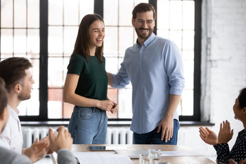 Smiling male employer introduce excited female newcomer to overjoyed diverse coworkers at office briefing, happy businessman welcome new worker at team meeting in boardroom, introduction concept