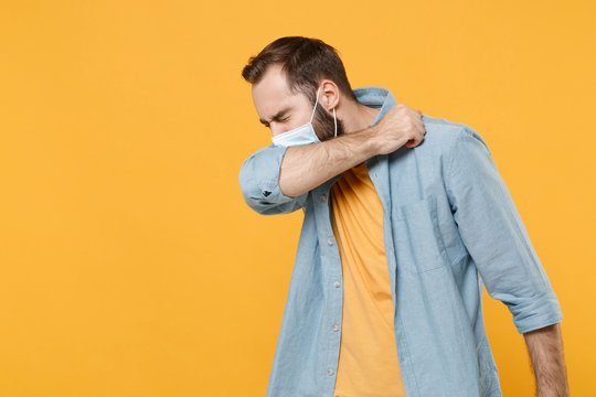 Young man in sterile face mask posing isolated on yellow wall background. Epidemic pandemic spreading coronavirus 2019-ncov sars covid-19 flu virus concept. Coughing or sneezing, covering with elbow.