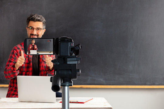 E-Learning . Adult man teacher is filming movie for online education.