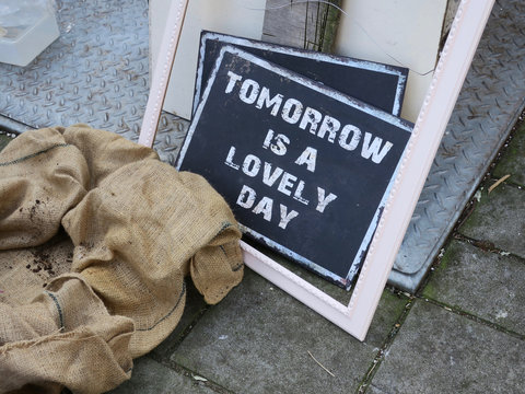 tomorrow is a lovely day, saying laying on the street near the garbage bin