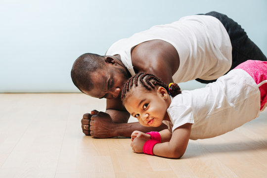 Father and daughter staying in shape in isolation, doing plank
