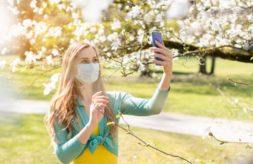 Woman taking a selfie with her phone in spring during Covid-19 crisis