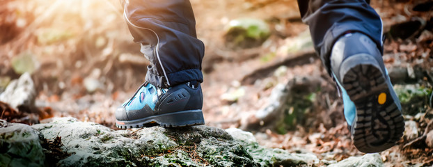 Hiking boots detail in summer light rocks mountains.