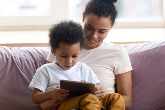 Happy african american mother sitting with son on couch looking at tablet device. Smiling diverse family engage in online shopping with boy together. Mom and chilld wathcing on smartphone.