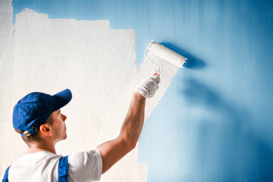 Painter painting a wall with paint roller.