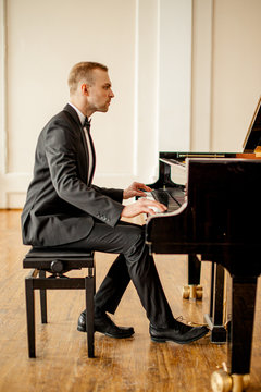 young caucasian male pianist perform classical music, man practice playing piano before his first concert or performance on a stage