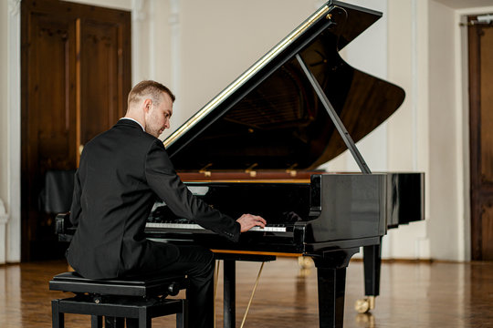 young handsome caucasian man in formal elegant suit gracefully play piano. professional pianist perform classic music
