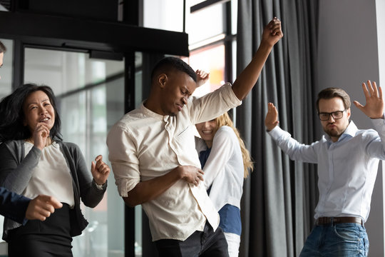 Excited happy multiracial businesspeople have fun engaged in activity in office together, overjoyed diverse colleagues dance celebrate successful business project, Friday celebration concept