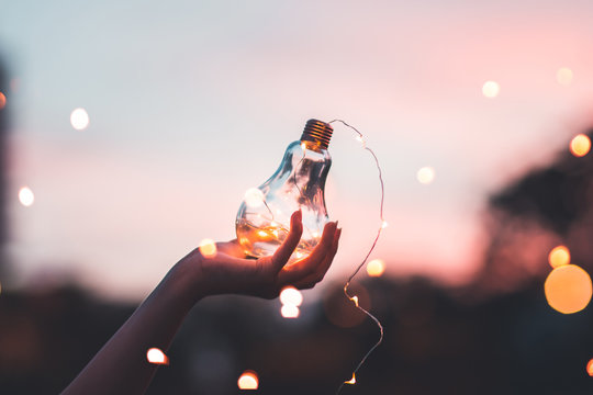Close-up Of Woman Holding Illuminated Light Bulb Against Sky At Night