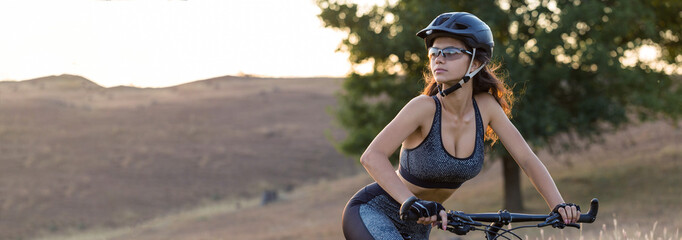 Girl on a mountain bike on offroad, beautiful portrait of a cyclist at sunset, Fitness girl rides a modern carbon fiber mountain bike in sportswear. Close-up portrait of a girl in a helmet and glasses Fototapete