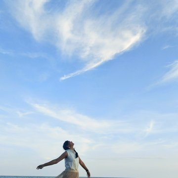 Woman With Arms Outstretched Standing Against Sky