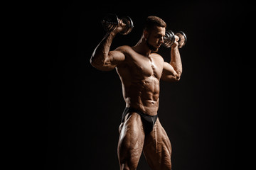 Muscular athletic bodybuilder fitness model posing and training with dumbbells. Isolated on black. Sport photo with dramatic light