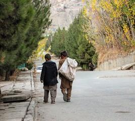 Rear View Of Boys Walking On Road