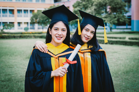 Portrait Of Female Friends Wearing Graduation Gowns Standing At Lawn