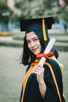Portrait Of Smiling Young Woman Wearing Graduation Gown Holding Certificate At Lawn