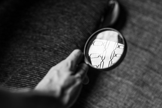 Cropped Image Of Hand Holding Magnifying Glass Over Book