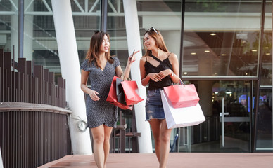 Women holding shopping bags outdoors Happy woman with shopping bags enjoying in shopping. Consumerism, shopping, lifestyle concept