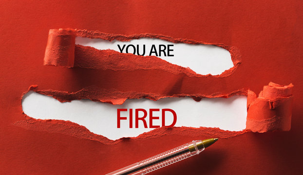 Red torn paper with inscription you are fired and pen close up