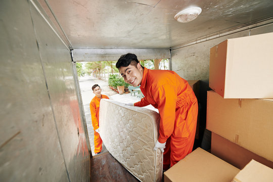 Smiling moving service workers in overalls loading heavy bed mattress in truck